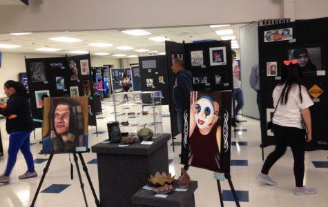 People mingle around the art work