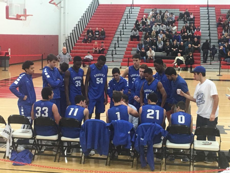 The+boys+baskeball+team+huddles+around+Coach+McCarty+during+a+timeout+in+their+game+at+Deerfield+on+Dec.+2.+The+Cougars+lost+to+the+Warriors+65-30.