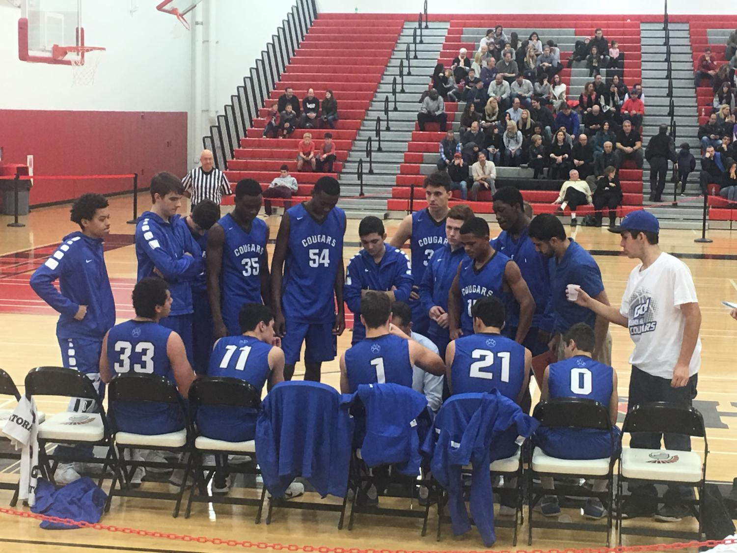The boys baskeball team huddles around Coach McCarty during a timeout in their game at Deerfield on Dec. 2. The Cougars lost to the Warriors 65-30.