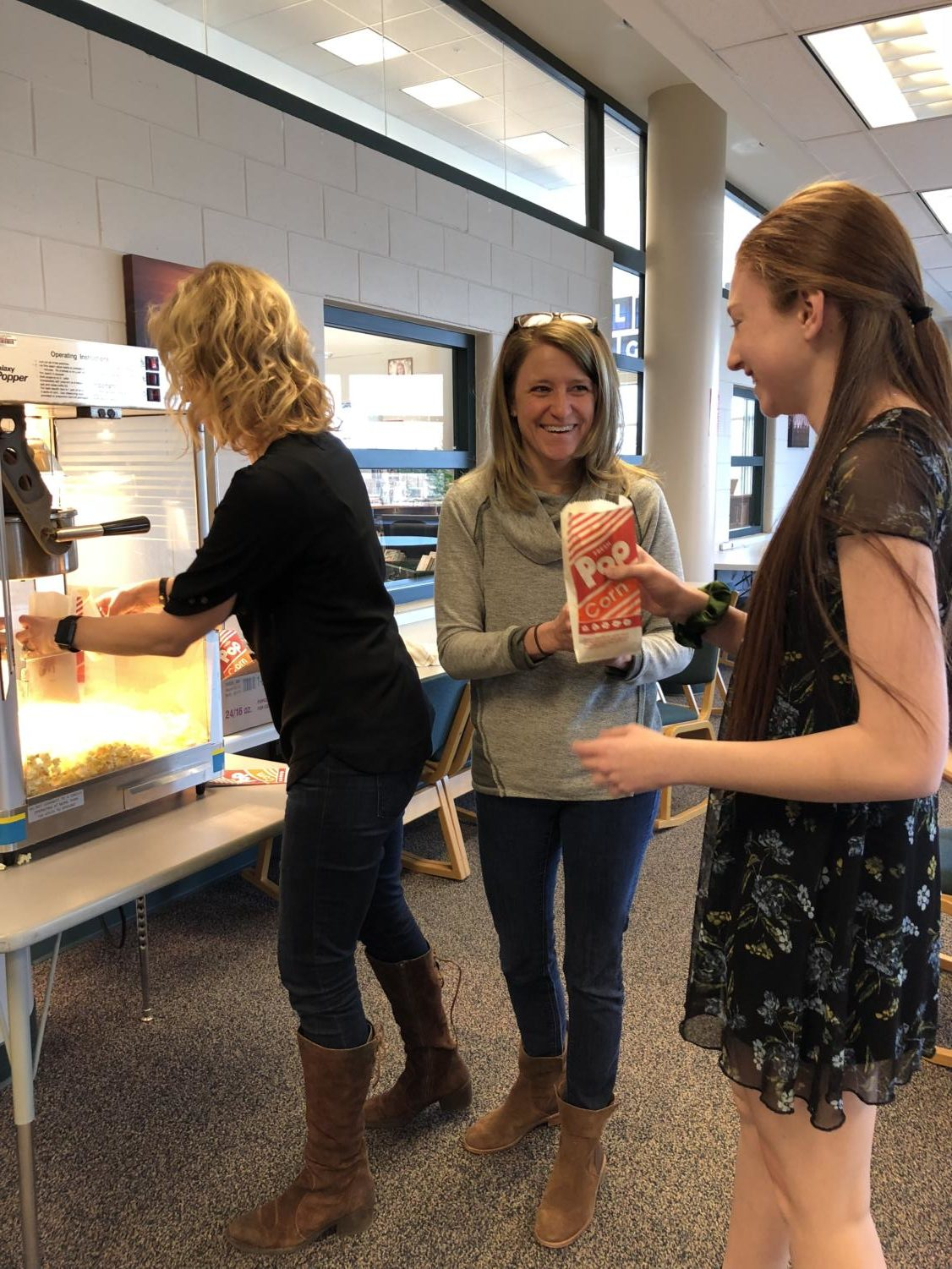 Caitlin Fagel (11) receives popcorn from Ms. Curry  and Ms. Bellito on a special day where popcorn was served at Camp Khan.