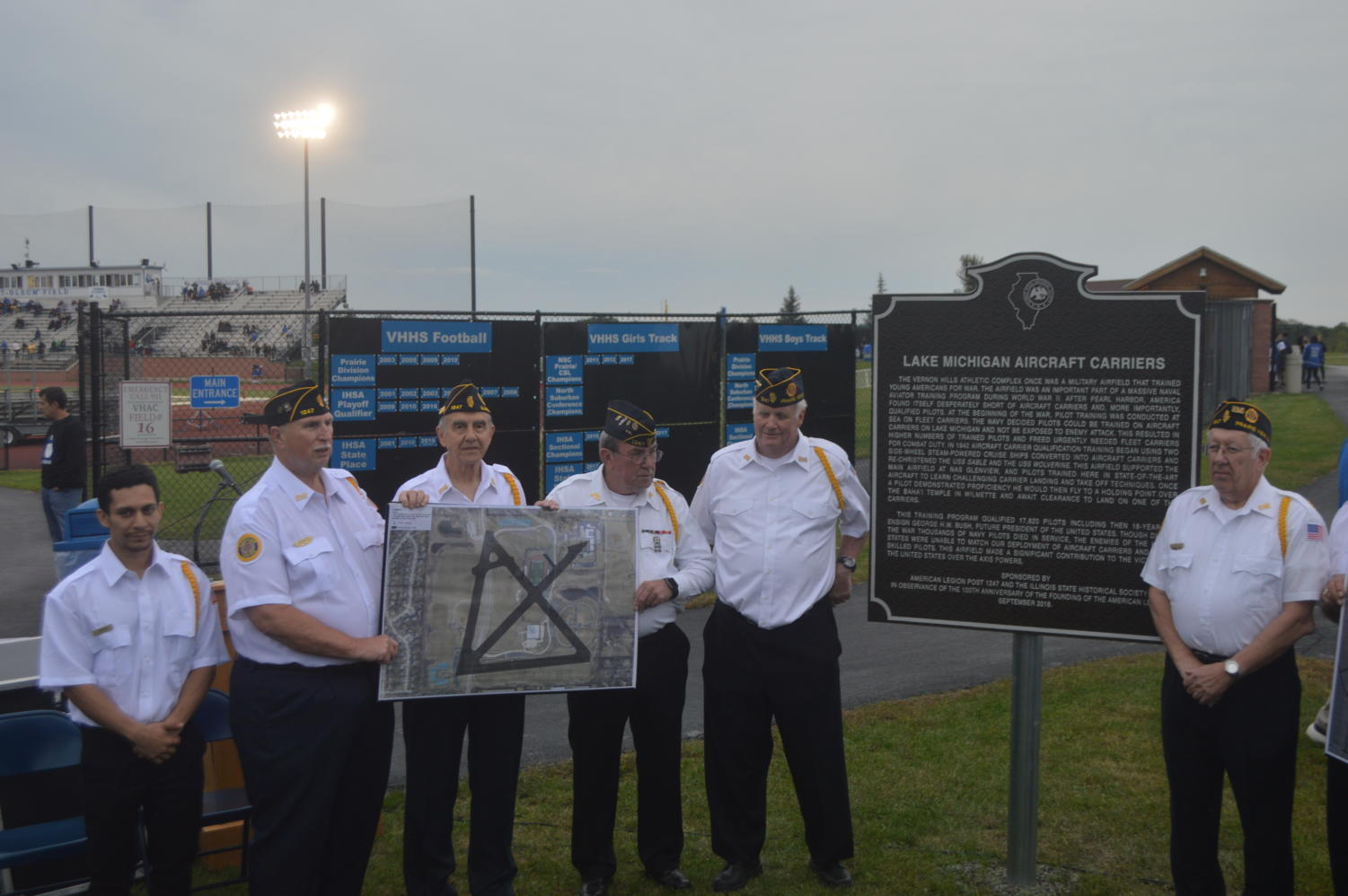 Six veterans pose next to the new historical marker outside of Rust-Oleum Field.