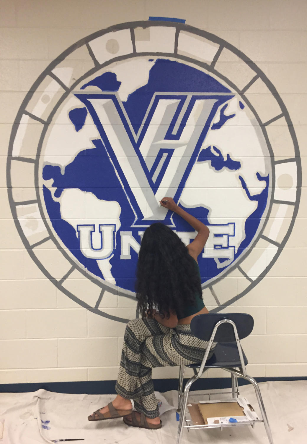 Akurati paints a VH Unite mural in the Fine Arts hallway.