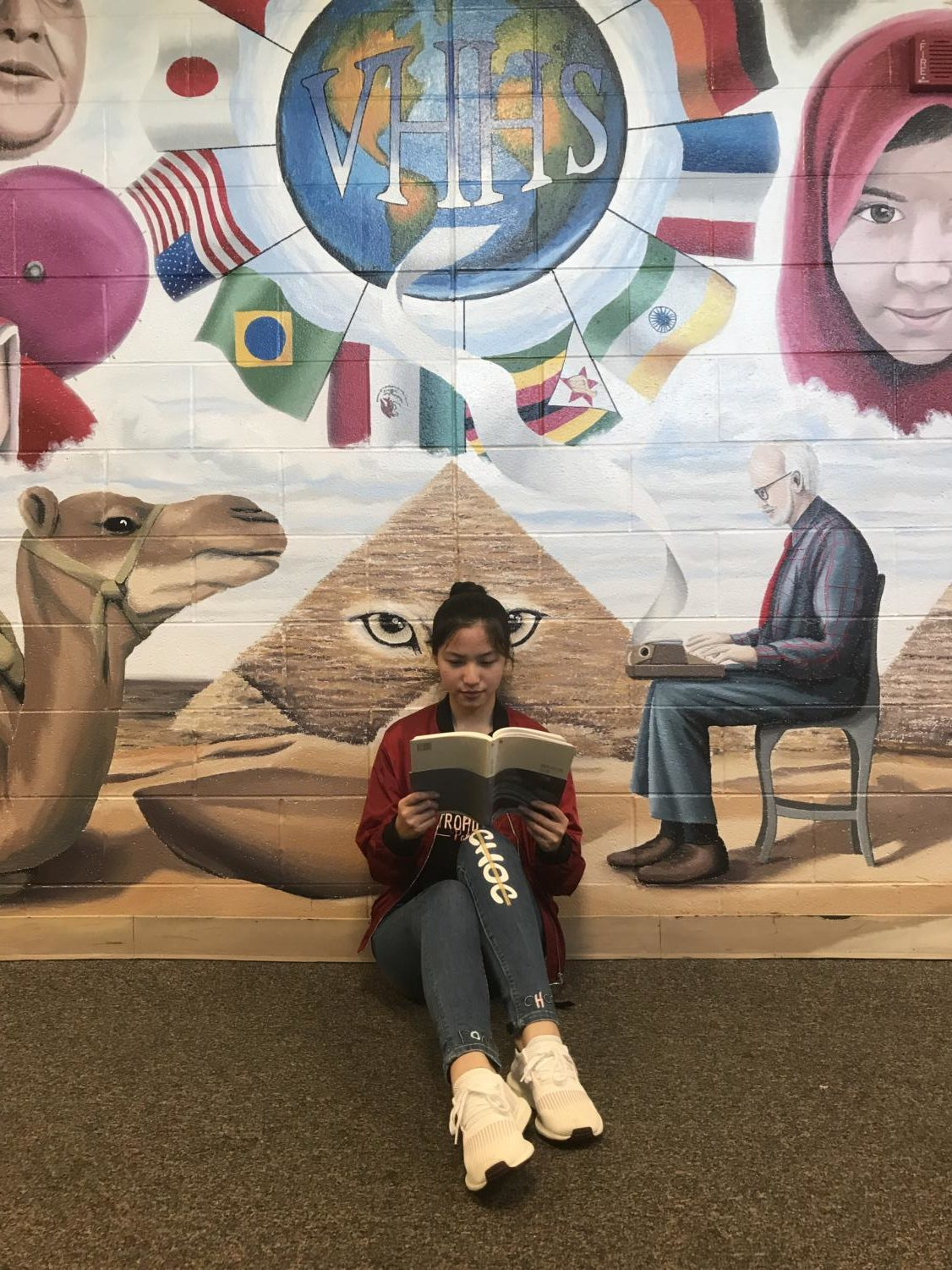 Keija Li sits in front of a school mural. This summer, she moved from China to Vernon Hills.