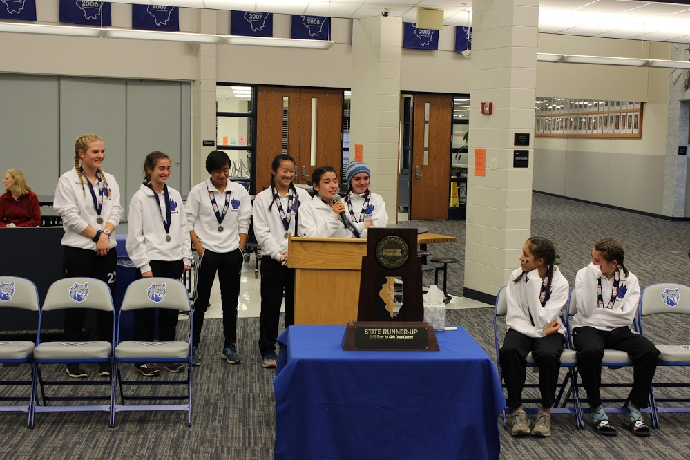 The Girls Cross Country team stands in front of their trophy.