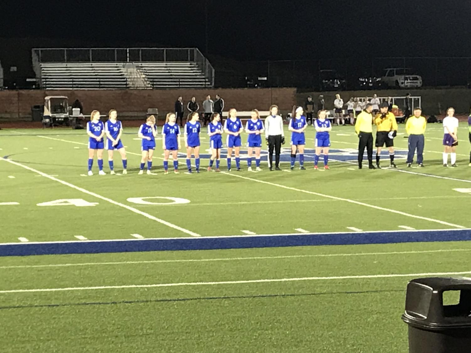 Starters for the girls soccer team line up for the National Anthem prior to their game against Wauconda High School.
