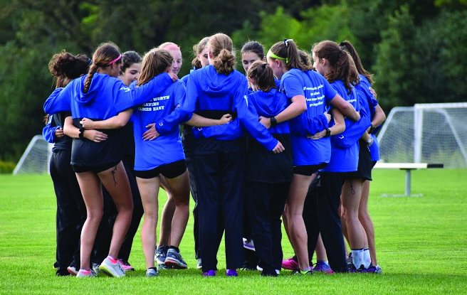 A+large+number+of+girls+on+the+varsity+cross+country+team+huddle+together+in+a+circle+with+their+arms+around+each+other.