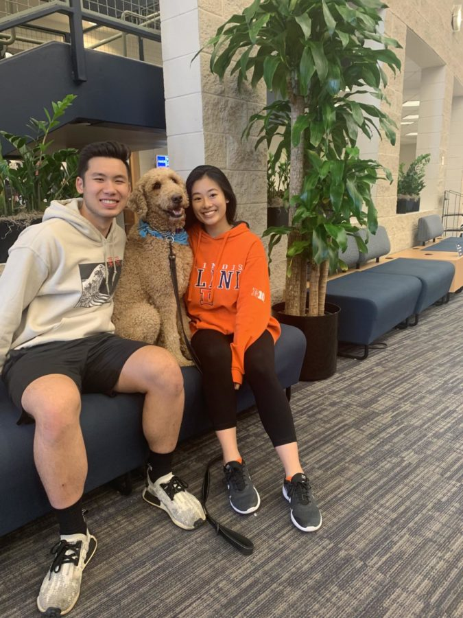 Students Justina Chua (right) and Alex Tantasook (Left) sit next to Basil the dog