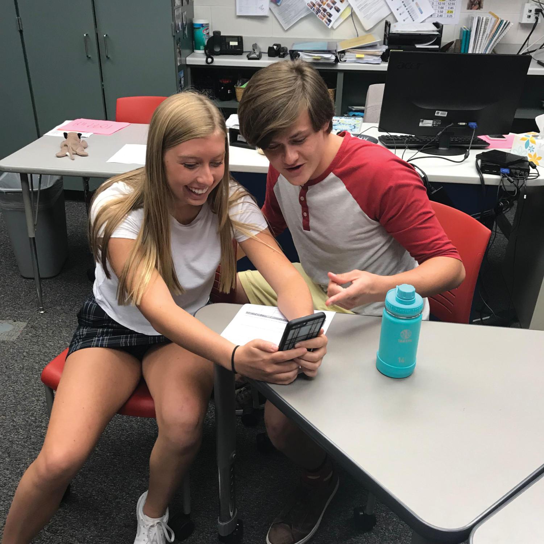 Kayla Mcnamara (left) shows Jacob Zimmerman (right) a Tik Tok video after class