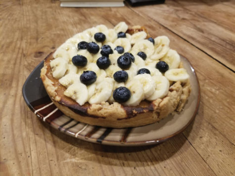The pumpkin pie on a plate with bananas and blueberries on top.