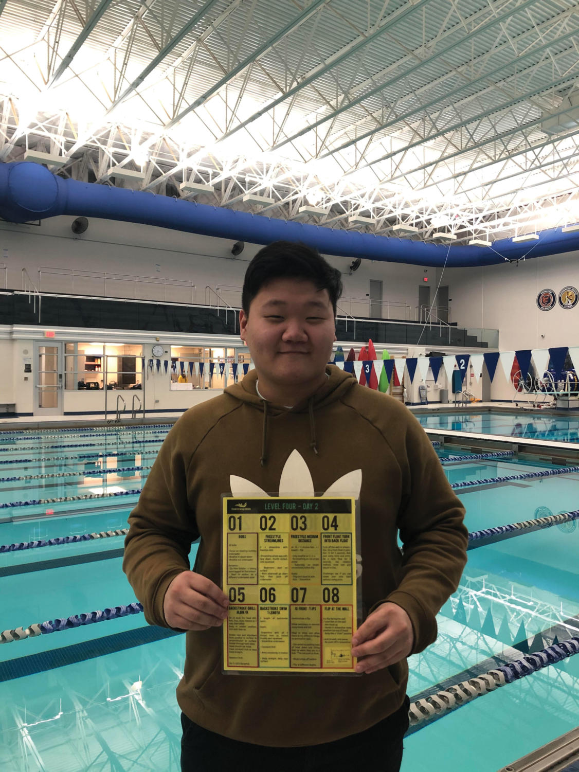 Jun poses in front of the school's pool.