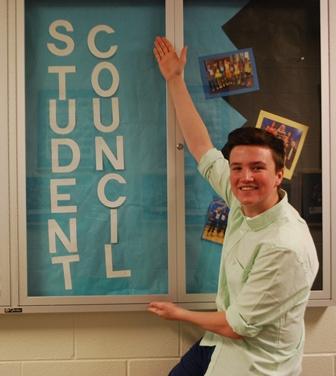 Morgan McDonough (11) poses by Student Council showcase