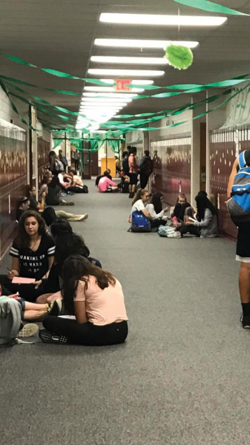 This is a photo of students sitting in circles with their friends in the hallway.
