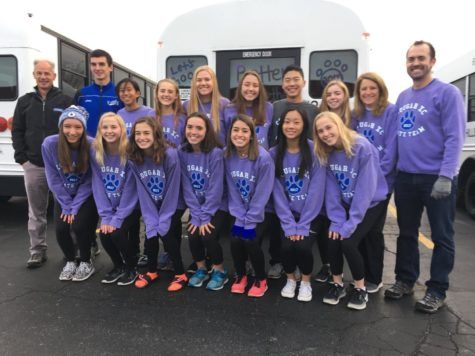 The girls and boys cross country team poses in front of their bus that will take them to state