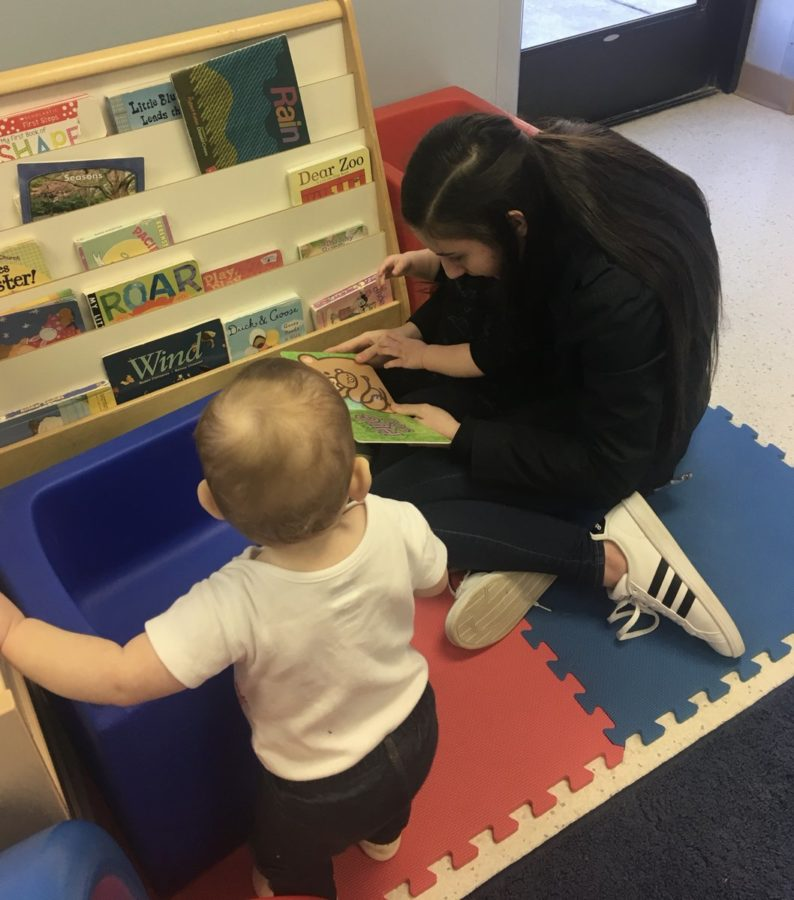Ruth Damianov reads books to the toddlers at Condell Child Day Center.