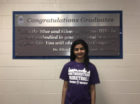 Rhea smiles in a Northwestern tshirt in front of the graduate sign.