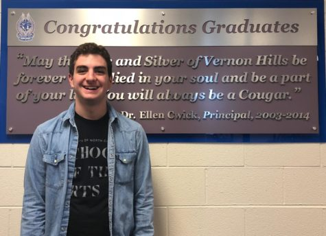 Sam Lemme stands in front of the VHHS graduate sign.