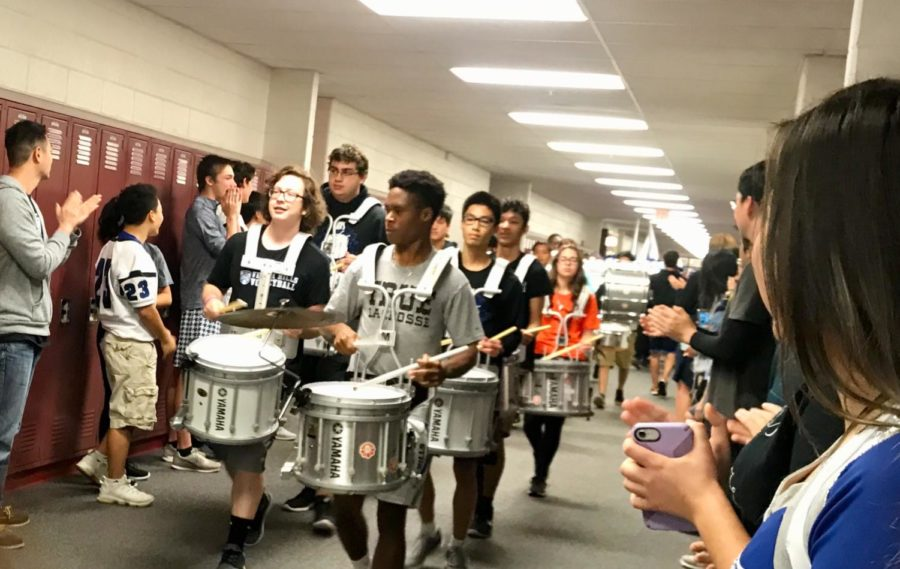 In this photo, the drum line is marching down the hallway with students on each side clapping