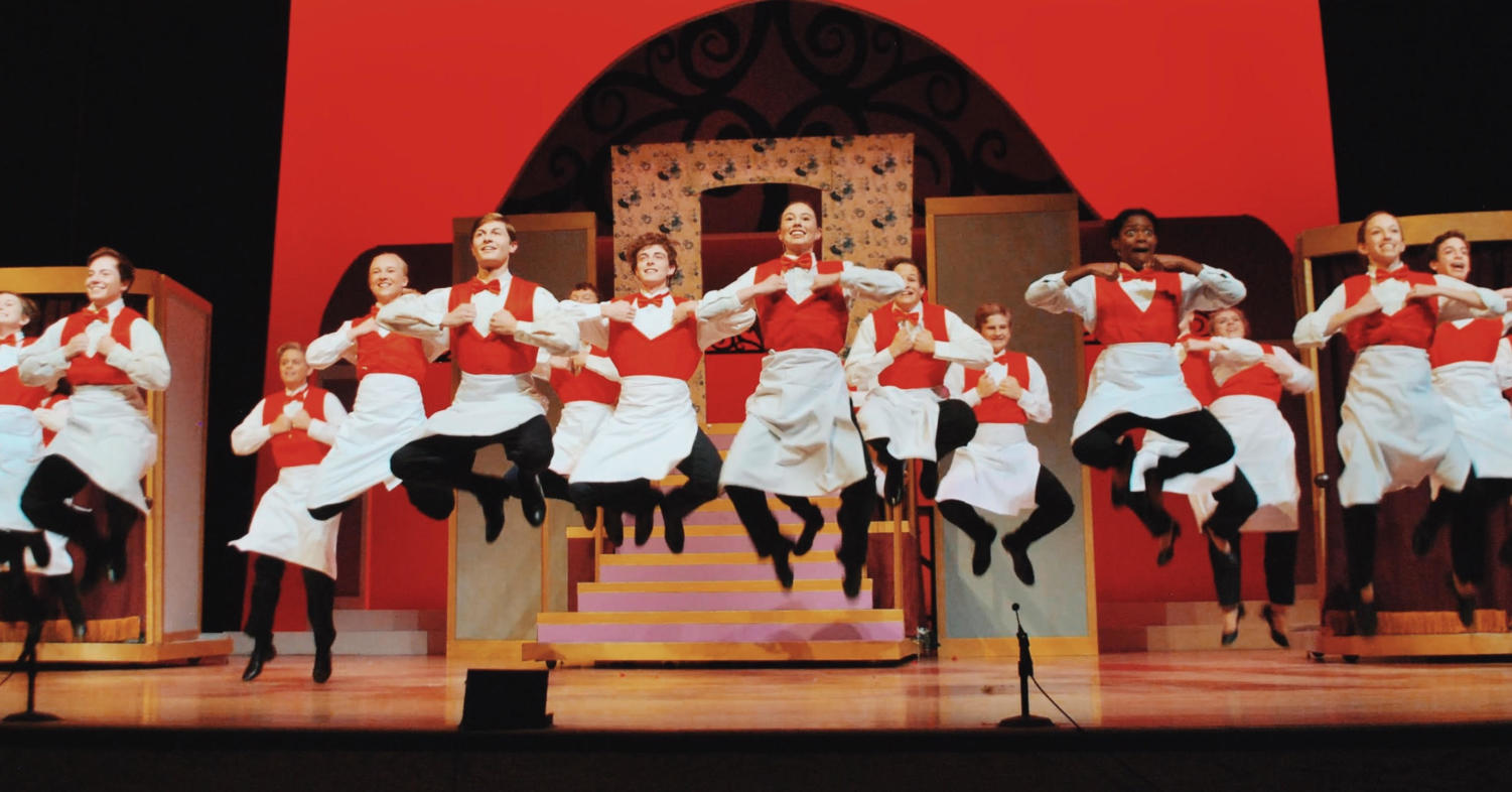 The cast of Hello Dolly jumps as they dance during the Harmonia Gardens Restaurant scene.