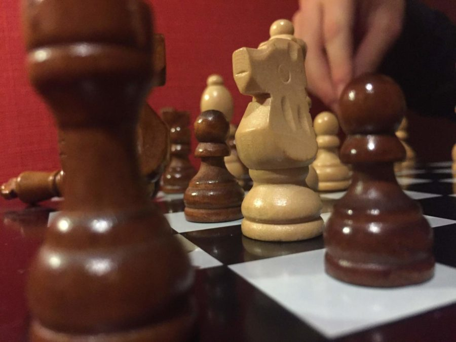 An image of a chess board, with a hand grabbing a chess piece in the background.