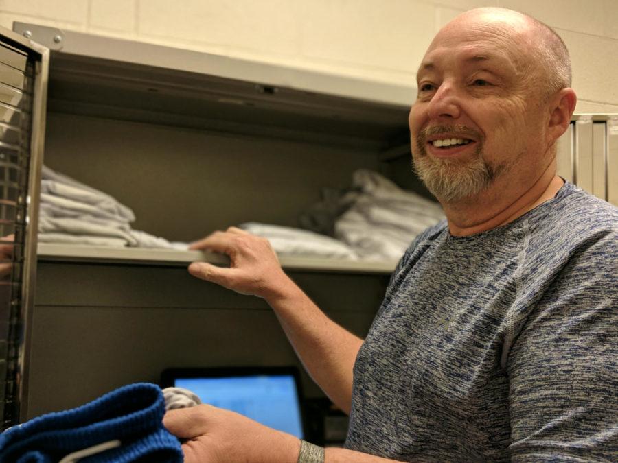 The+photo+shows+Mr.+Munro+reaching+into+a+locker+where+he+keeps+rental+gym+uniforms.