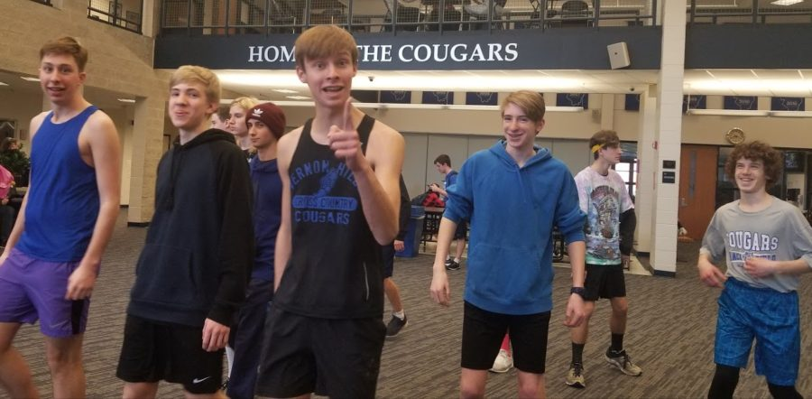 Six boys on the track team begin warming up inside for practice. They are smiling and one is pointing towards the camera.