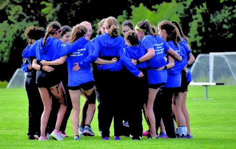 A large number of girls on the varsity cross country team huddle together in a circle with their arms around each other.