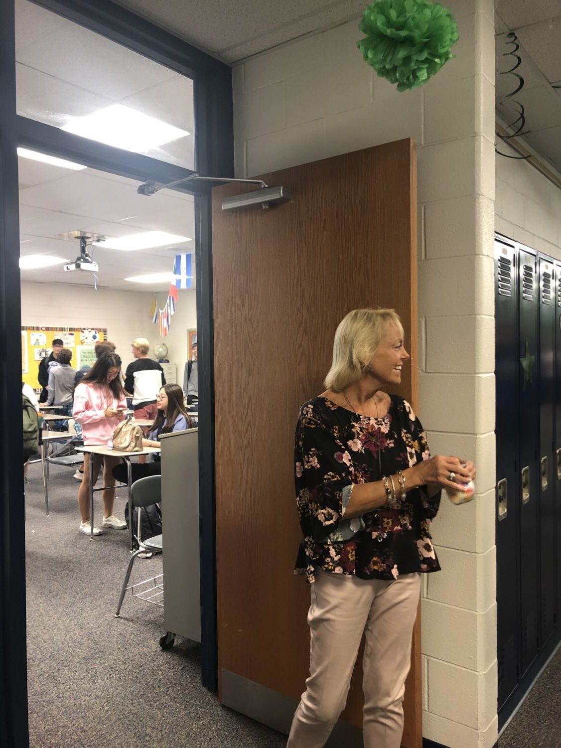 Ms. Schroeder stands outside a classroom, smiling