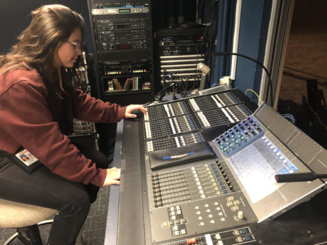Bella Pineda sits at a board that control sound and light.