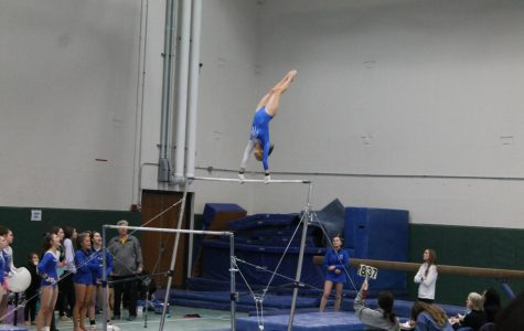 Dylan Sides (11) competes in the regional meet on the uneven bars.