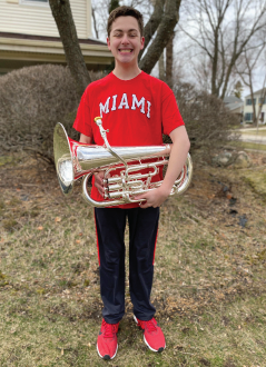 This is a photo of Benjamin Liber (12) posing with his euphonium while sporting his college shirt.