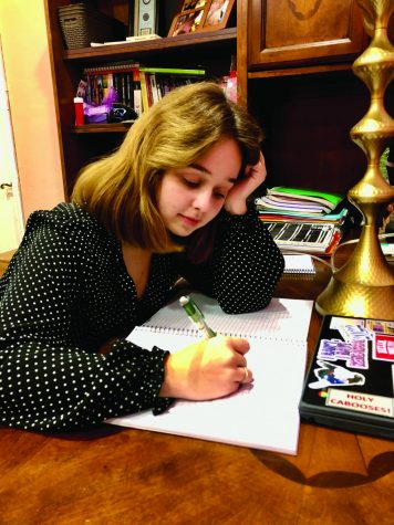 Anika Urbonas (11) writes a pitch for the Backlight Theater Company musical.