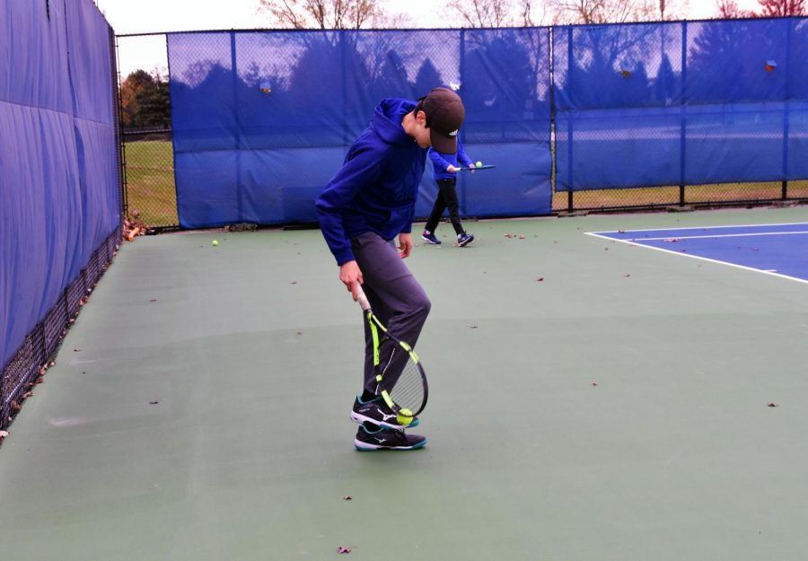 Student picking up ball with their foot.