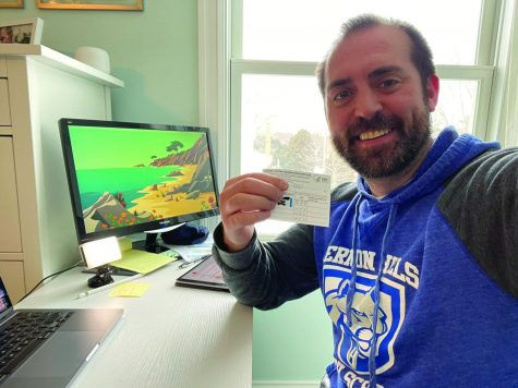 Mr. Wolf poses with his COVID Vaccine Card
