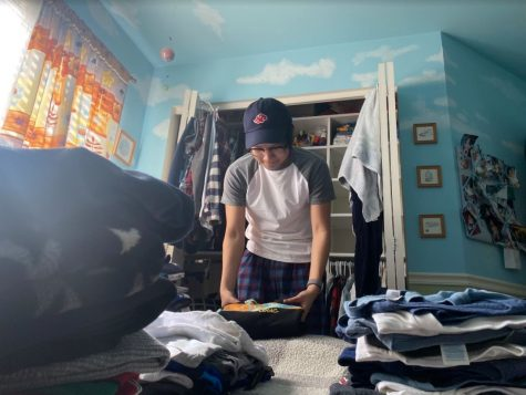Brandon Carido (12) sifts through old clothes to clean out his closet. He even stumbles across shirts of his from preschool!
