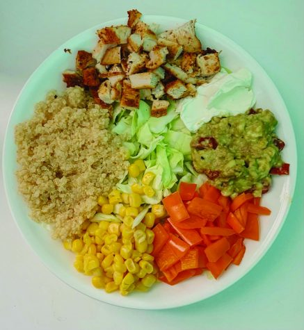 A nourish bowl featuring lettuce, chicken, quinoa, red bell pepper, lettuce and guacamole.