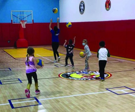 Marianna leaps as she tosses her basketball into the basketball hoop. There is a line of three kids behind her preparing to shoot their basketballs as well. One small girl is running towards the back of the line with her ball.