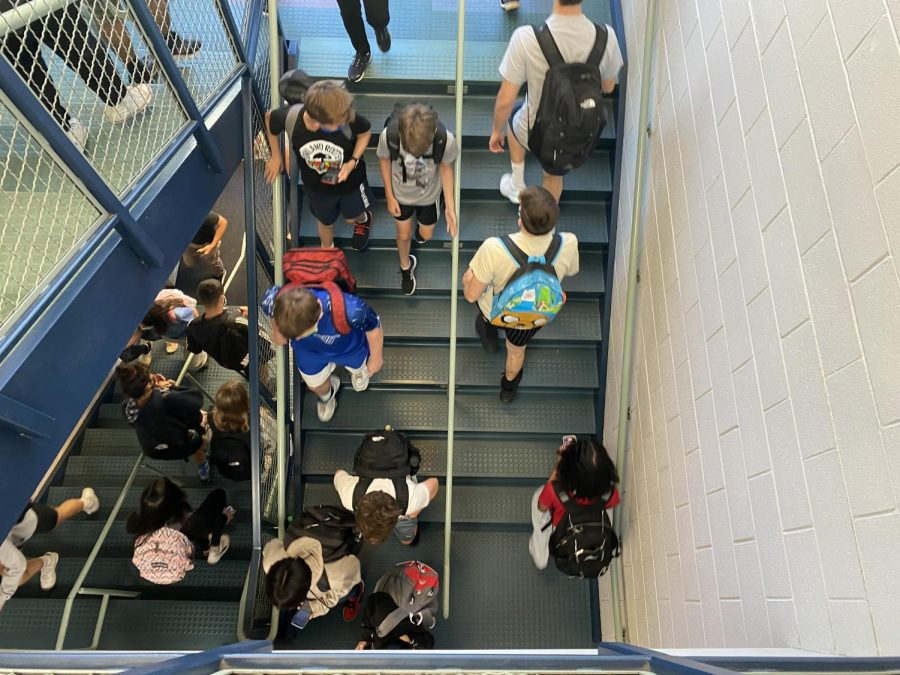 Students walk up and down the stairs during a passing period.