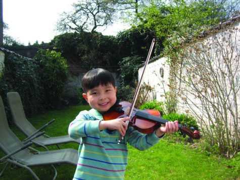 This is a photo of Ian Joe playing the violin outside at a young age.