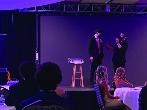 A student and magician stand on stage together.