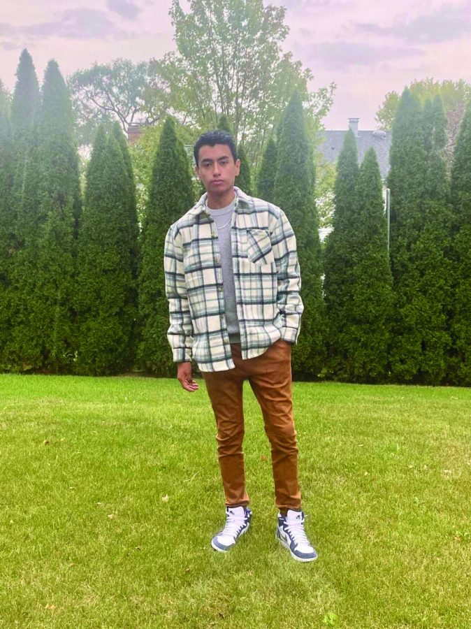 Erick Herrera stands in his background wearing a flannel and joggers with a grey t-shirt